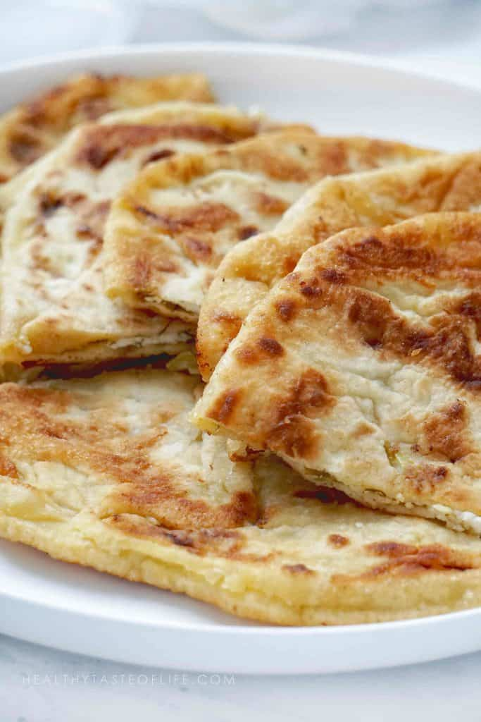 This homemade stuffed flatbread recipe makes crisp as well as soft golden brown flatbread stuffed with potato (vegan option), cheese filling or sweet filling (apples and sour cherries). No yeast, easy stuffed flatbread - great served as an appetizer with dips, make ahead finger food, or as a side dish along with your favorite dinner or lunch. The perfect party snack / appetizer for large crowds or family dinners.