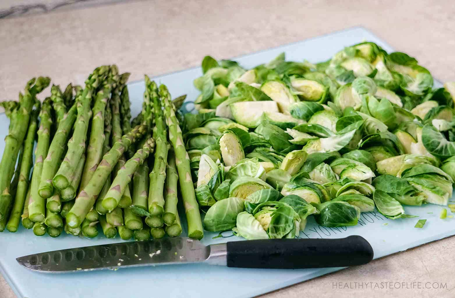 Chopped quartered brussels sprouts and asparagus prepared for roasting