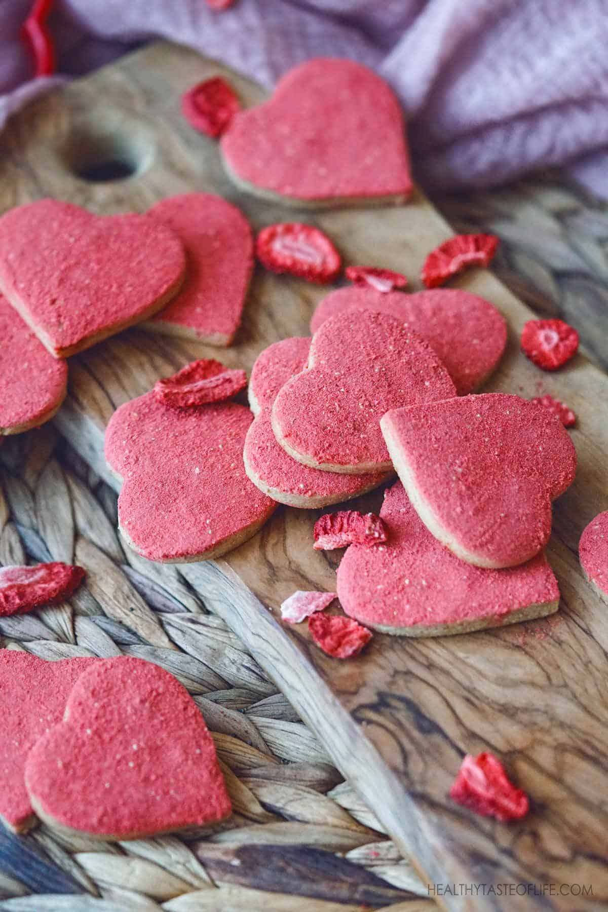 Make these healthy gluten free Valentine cookie treats for your Valentine's Day party! This heart shaped vegan gluten free cut out sugar cookies are flavored with freeze dried strawberries with a nice crisp around the edges and hints of buttery shortbread notes. #veganglutenfree #sugarcookies #valentine #heartshaped #cutoutcookies #glutenfree