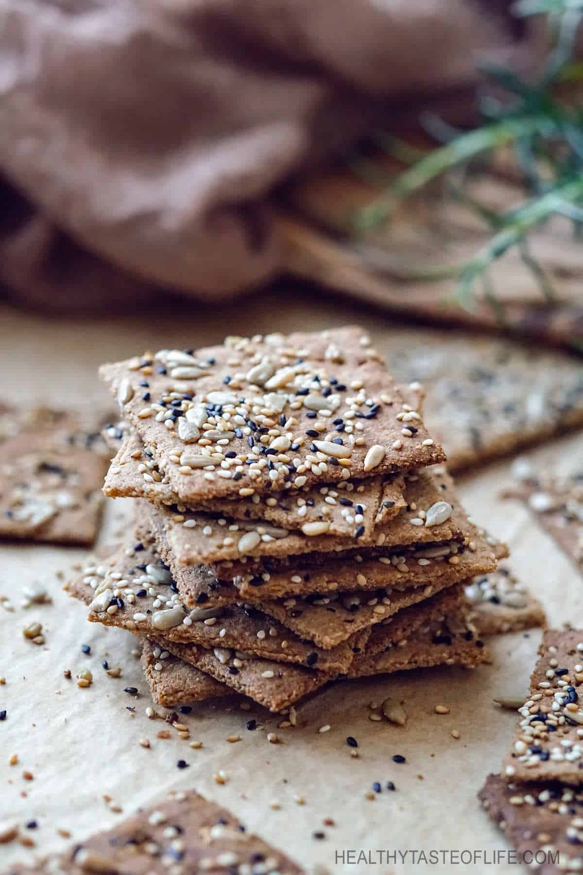Crispy homemade keto low carb crackers recipe that's also dairy free, gluten free, grain free, nut free, paleo and vegan. Made with flax seeds, sunflower seeds, sesame seeds and a few other healthy ingredients. A low carb snack great for anyone who is following a dairy free keto diet. #keto #lowcarb #crackers
