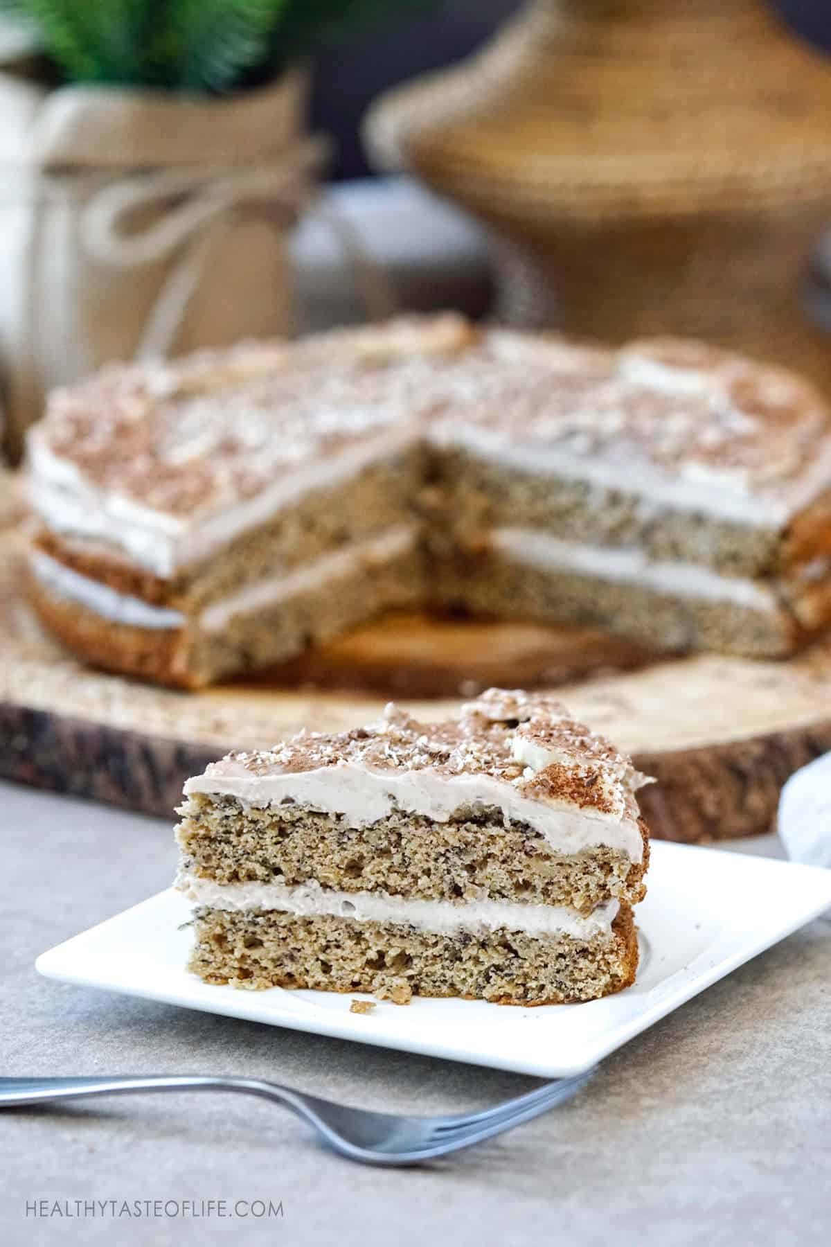 Banana cake gluten free dairy free recipe without refined sugar. A slice of layered gluten free banana cake with dairy free frosting decorated with fresh bananas and shaved chocolate.