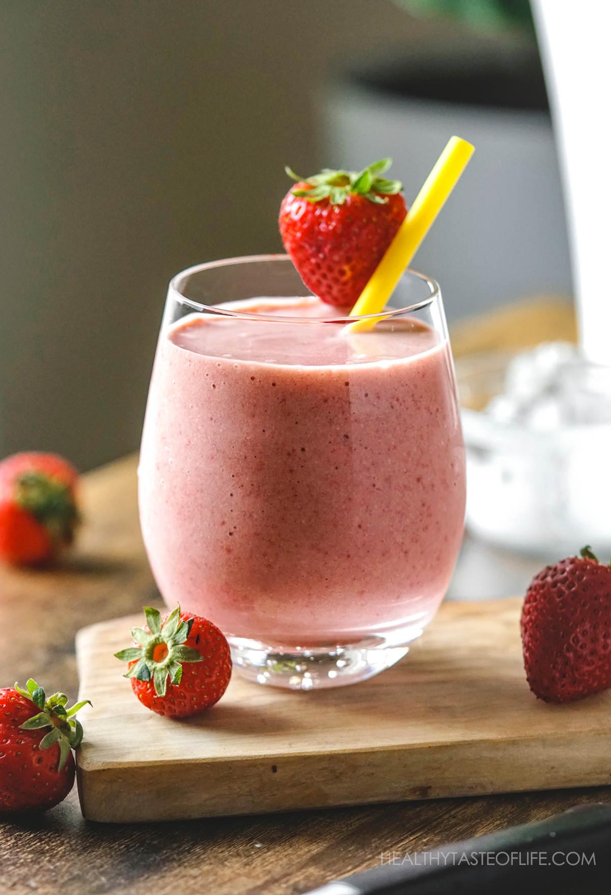 Strawberry banana milkshake dairy free vegan in glass and garnished with a strawberry.