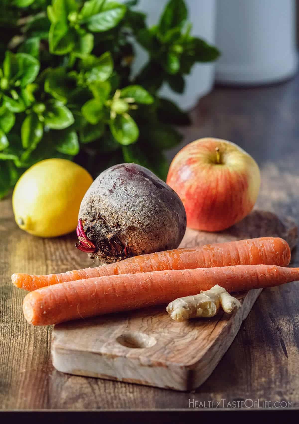 Whole beet carrots apple lemon ginger on prepared for juicing.