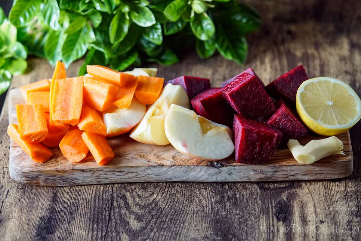 Chopped beets carrots apple ginger and lemon on a board.