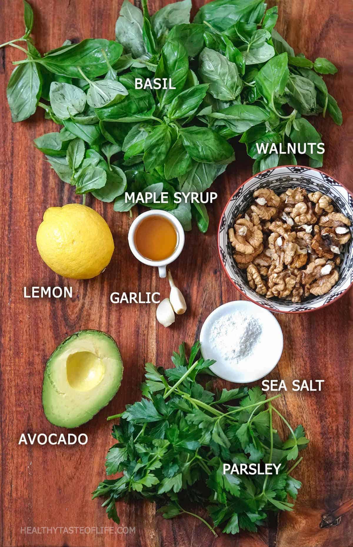 Ingredients for making creamy basil pesto vegan gluten free - avocado, walnuts, parsley, lemon, garlic, maple syrup and sea salt.