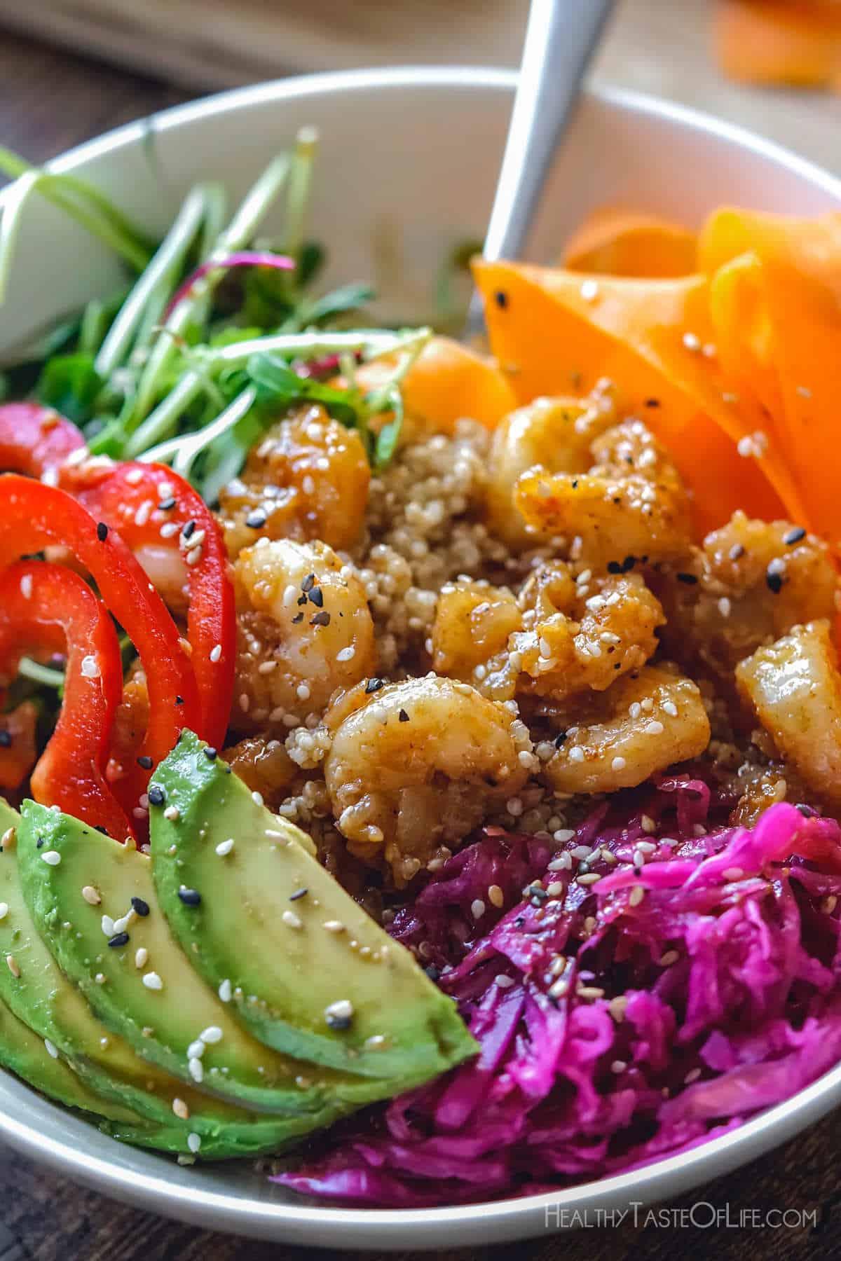 Shrimp quinoa poke bowl with sauce.