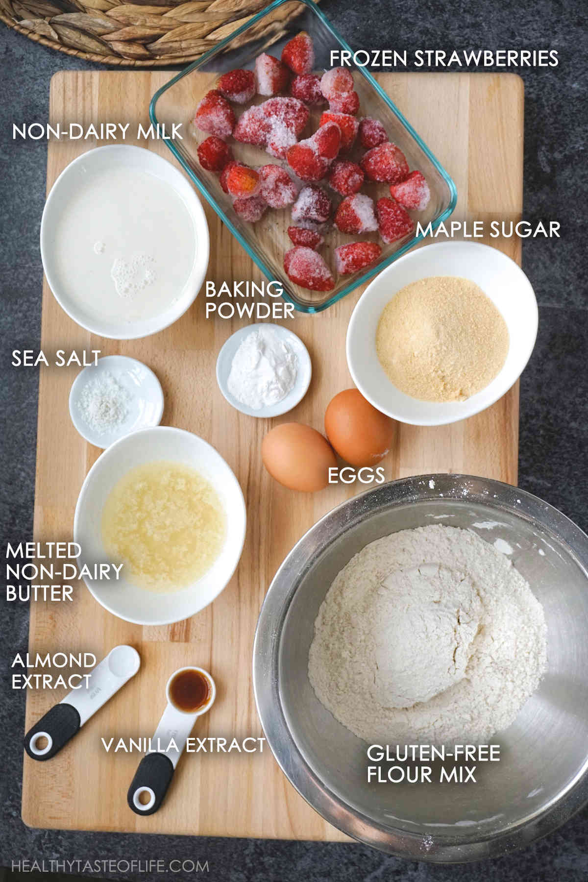 Ingredients for strawberry muffins displayed on a board.