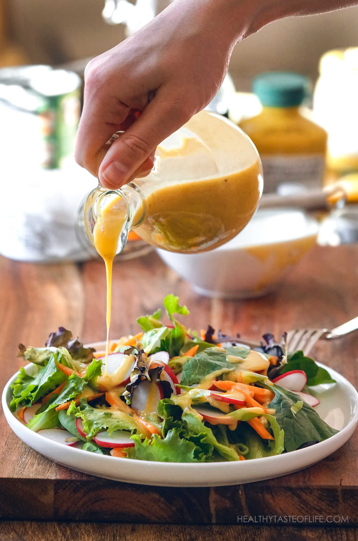 Pouring the honey mustard sauce over a plate of salad.
