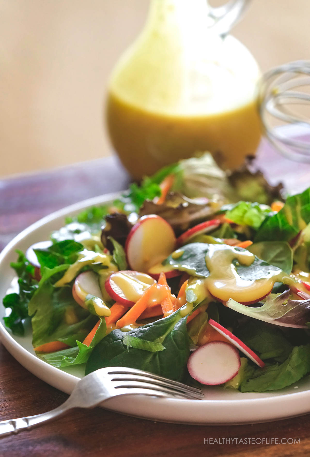 A plate of salad drizzled with vegan honey mustard sauce.