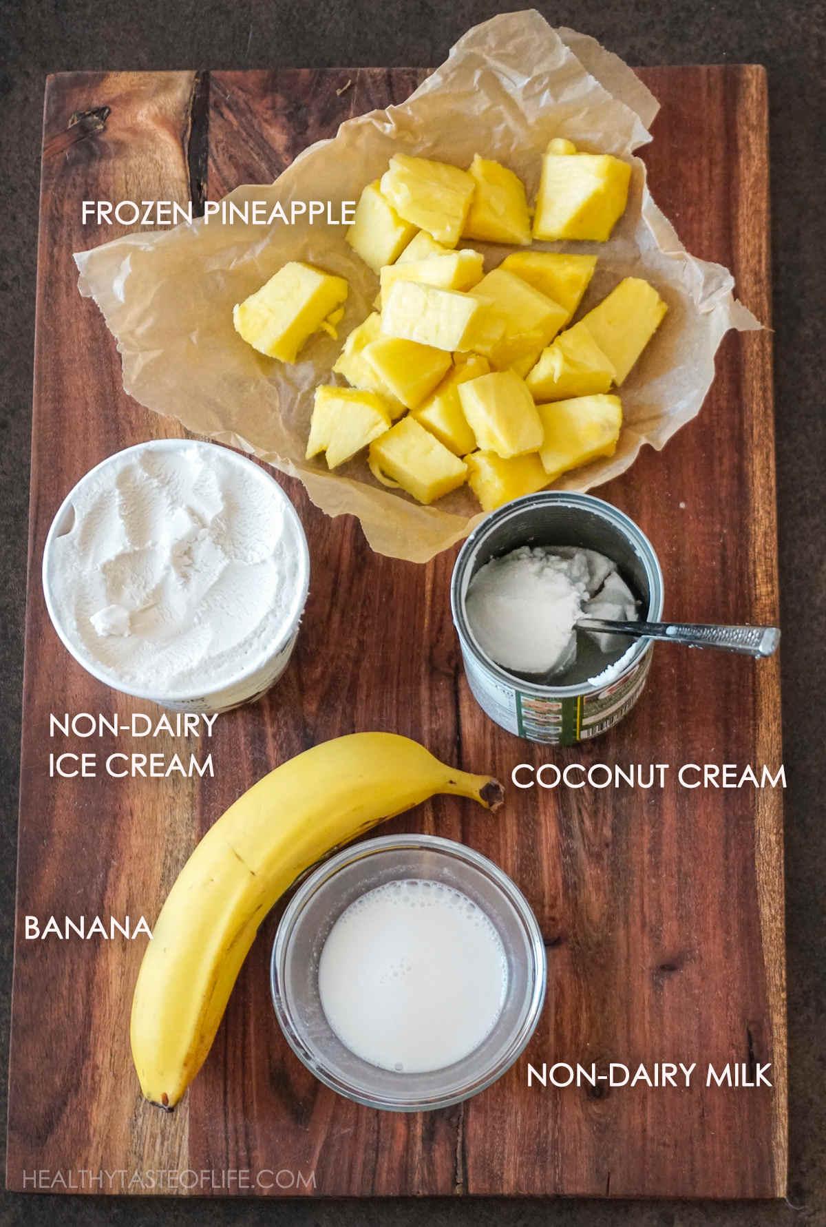 Ingredients for vegan pineapple milkshake displayed on a board.