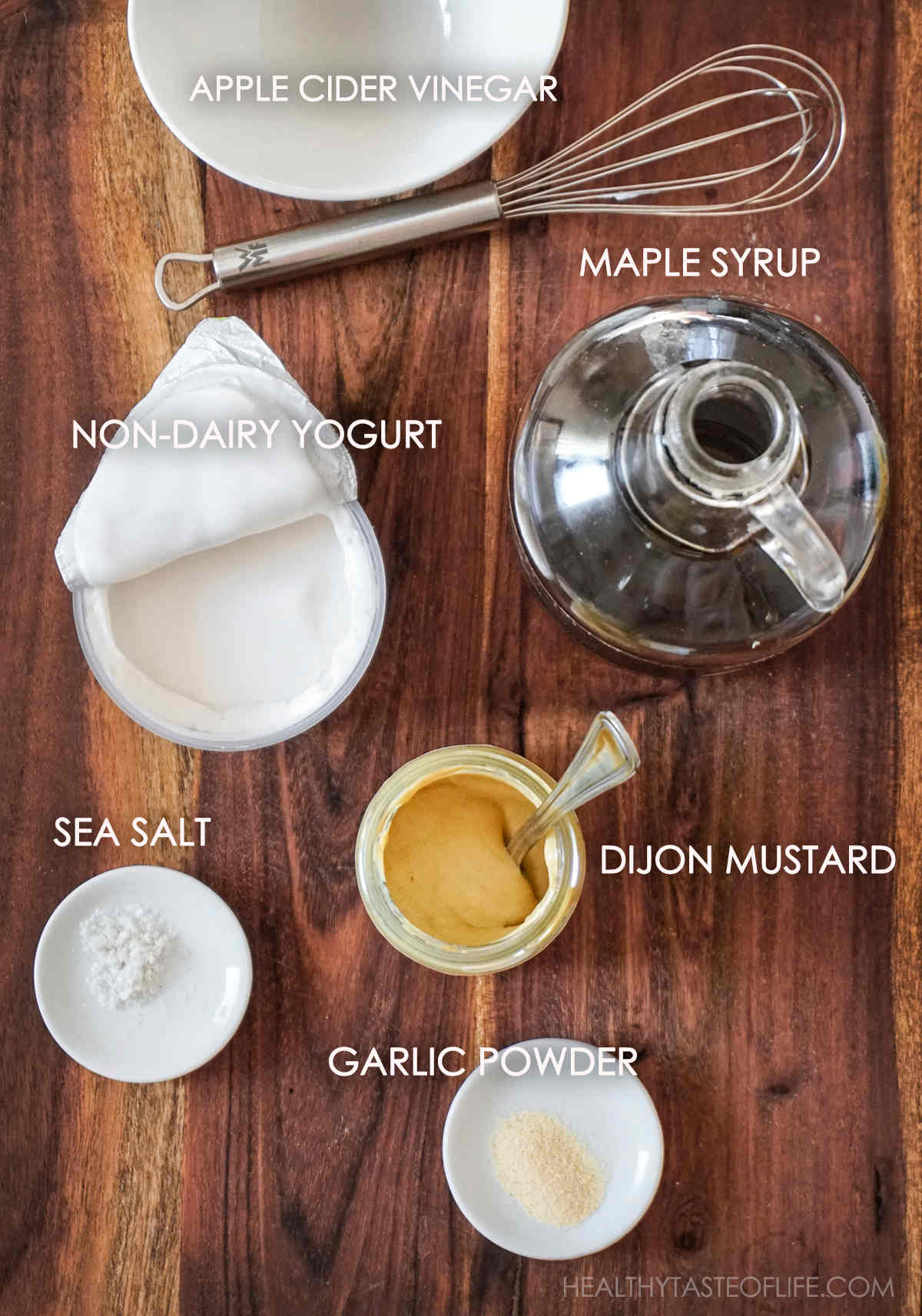 Ingredients for vegan honey mustard dressing displayed on a board: Dijon mustard, maple syrup, dairy free yogurt, apple cider vinegar garlic powder, sea salt.