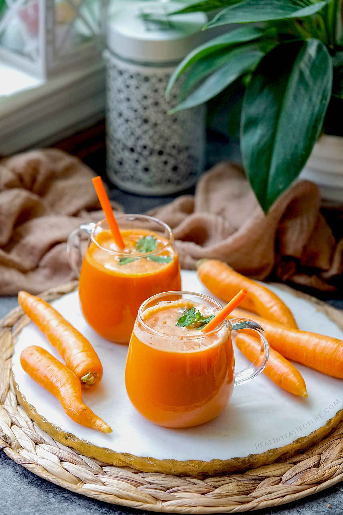 Carrot juicing - homemade carrot juice served in glass mugs.