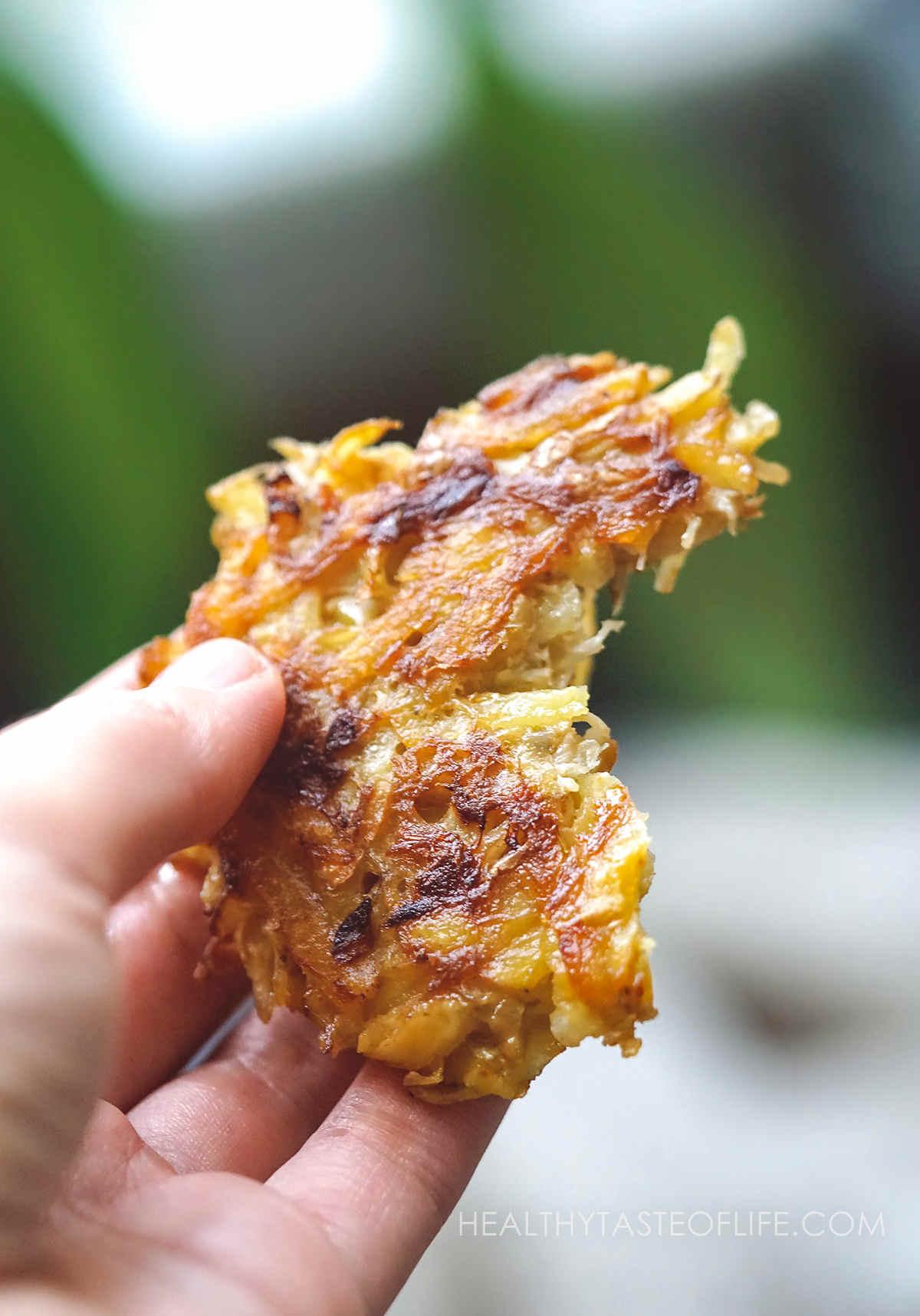 Bitten potato fritter held in a hand.