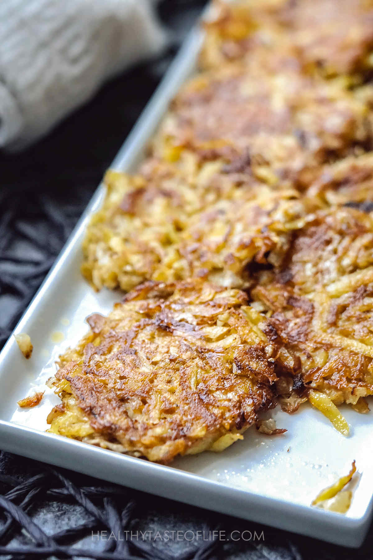 Golden crispy potato fritters with crab meat on a platter.
